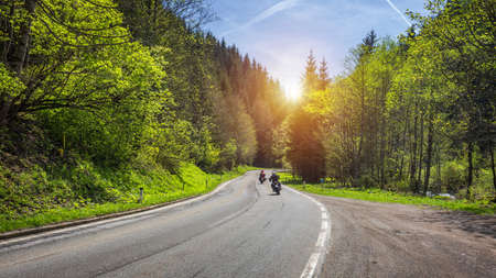 Photo pour Bikers on mountainous highway, biker on the road in sunset light riding on curve road pass across Alpine mountains, extreme lifestyle, freedom concept. Austria, Alps - image libre de droit
