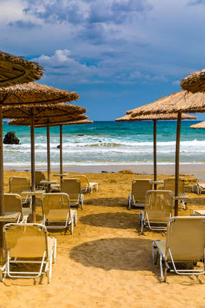 Photo pour Summer vacation destination. Straw sunshades and sunbeds on the empty pebble beach with sea in the background. Vacation And Tourism Concept. Sunbeds On The Paradise Beach. Umbrellas and sunbeds. - image libre de droit