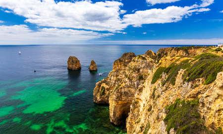 Photo pour Panoramic view, Ponta da Piedade near Lagos in Algarve, Portugal. Cliff rocks and tourist boat on sea at Ponta da Piedade, Algarve region, Portugal. Ponta da Piedade, Algarve region, Portugal. - image libre de droit