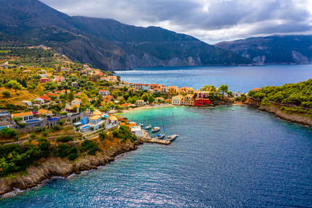 Photo pour Turquoise colored bay in Mediterranean sea with beautiful colorful houses in Assos village in Kefalonia, Greece. Town of Assos with colorful houses on the mediterranean sea, Greece. - image libre de droit