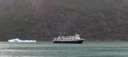 Tracy Arm Fjord, Alaska, US - August 23, 2018: National Geographic's Sea Bird vessel drifting with a mountain and an iceberg behind it in Tracy Arm Fjord in Alaska, USA