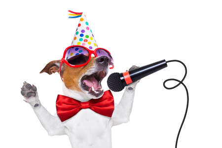 Photo for jack russell dog  as a surprise, singing birthday song like karaoke with microphone wearing  red tie and party hat  , isolated on white background - Royalty Free Image