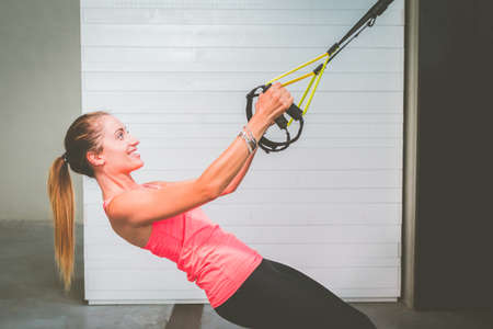 Beautiful girl training her arms with straps Fitness in the gym - Woman doing push-ups trains the upper body chest shoulders pectoral triceps