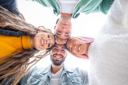 Photo pour Group of four teenagers looking down arm in arm - Multicultural group of young people having fun - Friends on summer vacation looking at camera and laughing hugging each other - image libre de droit
