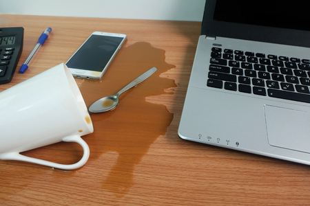 Foto de Coffee Cup spill out on Keyboard Laptop computer and calculator on wooden floor,Cause damage Accident computer repair concept. - Imagen libre de derechos