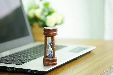 Foto de Wooden hourglass on a laptop computer, Managing time and countdown to deadline concept - Imagen libre de derechos