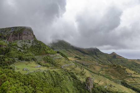 Summertime cloudy view of the Roches dos Bardoes basalt formation on Flores island in the Azores.