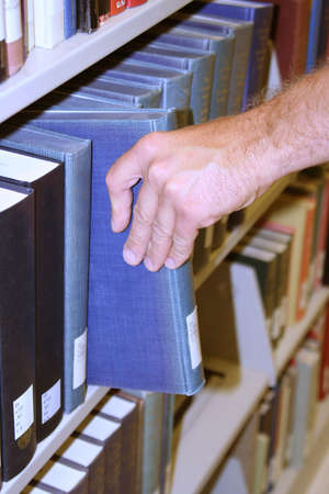 Man selecting book from shelf in library