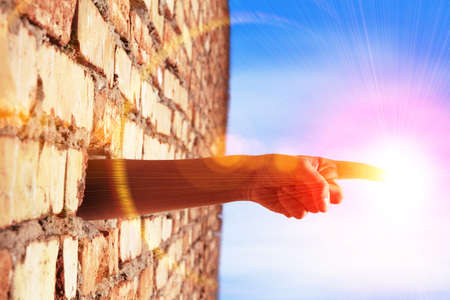 hand breaking wall to touch the sun