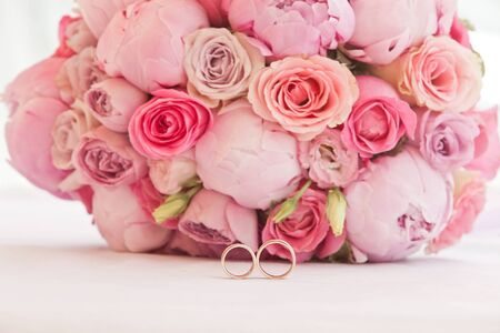 Photo pour beautiful bouquet of peonies and other pink flowers with wedding rings for newlyweds - image libre de droit