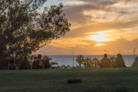 Photo pour MONTEVIDEO, URUGUAY, OCTOBER - 2015 - Young people watching the sunset from the top of hill in a park in front of river in Montevideo, Uruguay - image libre de droit