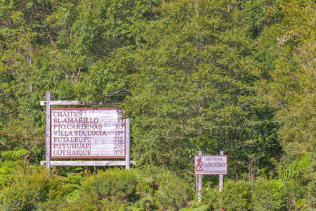 LOS LAGOS, CHILE, APRIL - 2017 - Travel information signpost at leafy forest in Caleta gonzalo, Chile