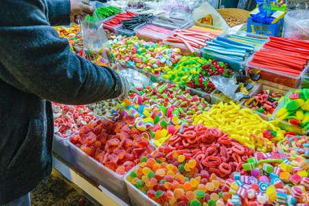 Foto de Person picking out colorful candies displayed at ancient jerusalem city - Imagen libre de derechos