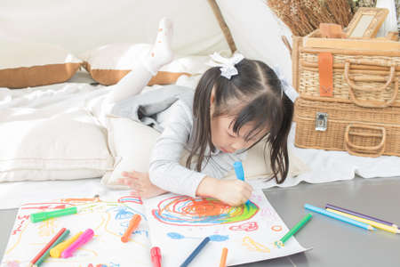Photo pour Asian little girl painting on paper in white room at home - image libre de droit