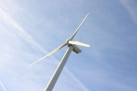 View of single windmill generating electricity against blue sky