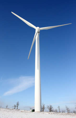 View of single windmill generating electricity against blue sky in a winter landscape