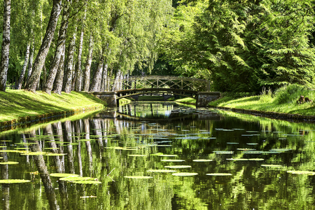 Beautiful bridge over the cross canal of the Schwerin Palace garden. Water landscape.