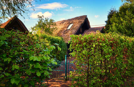 Photo for Boathouses with thatched roof and front yard in the green. - Royalty Free Image