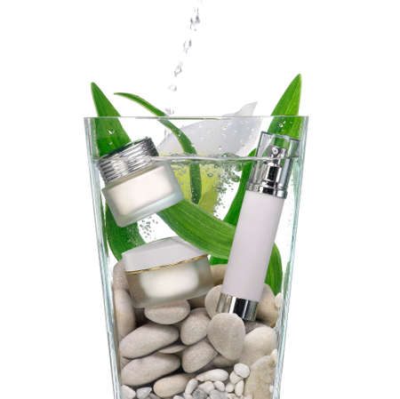Cosmetics in a vase of water with stones and green leaves