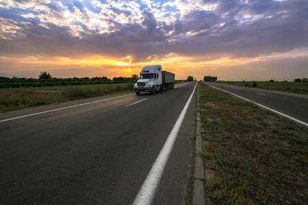 Photo for Big truck on a countryside road with dramatic sunset background.  - Royalty Free Image