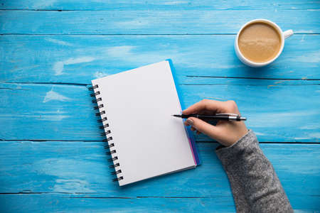 Photo for woman hand notepad and coffee on desk - Royalty Free Image