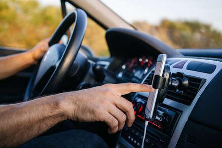 Photo pour Man using phone with hand while driving a car - image libre de droit