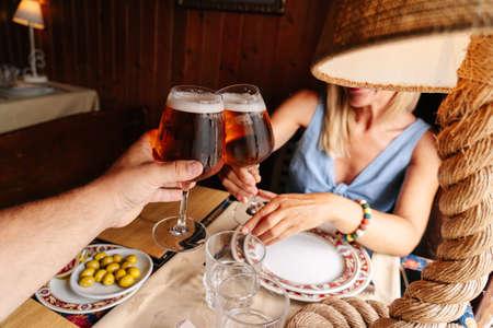 Foto de A beautiful caucasian blond woman toasting with beer restaurant next to a window - Imagen libre de derechos