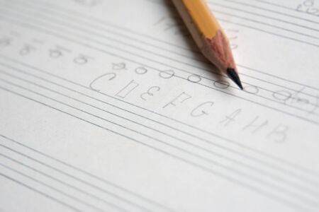 Photo pour pencil on a musical notebook close-up, abstract musical notes and chords, musical background - image libre de droit