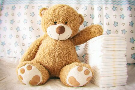 Photo for diapers with baby soft toy bear on the background of the nursery and crib, the concept of using diapers for babies, effect camera toy - Royalty Free Image