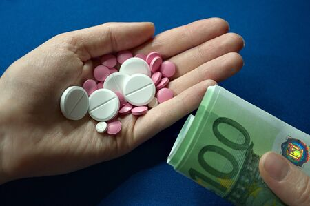 Photo for hand holding pills and hand holding money, expensive medicine, medical care not for everyone, medical insurance - Royalty Free Image