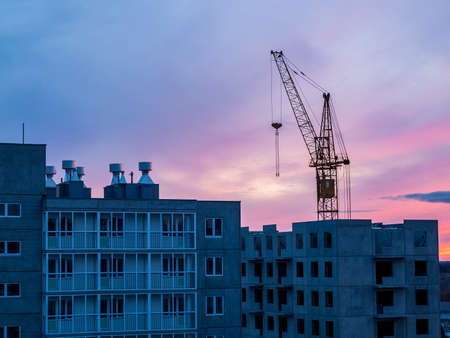Photo pour high-rise crane in the construction of high-rise buildings in the city district, against the background of the sunset - image libre de droit