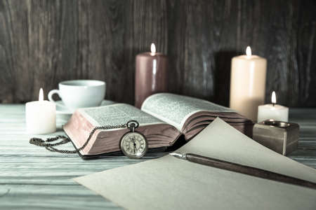 Candle and bible on wood background