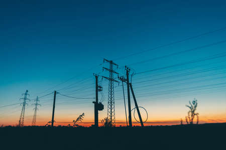 Photo for Power lines in field on sunrise background. Silhouettes of poles with wires at dawn. Cables of high voltage on warm orange blue sky. Power industry at sunset. Many cables in picturesque vivid sky. - Royalty Free Image