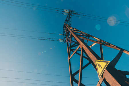 Photo for Power lines on background of blue sky close-up. Electric hub on pole. Electricity equipment with copy space. Wires of high voltage in sky. Electricity industry. Tower with lightning warning sign. - Royalty Free Image