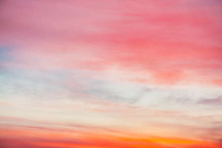 Sunset sky with pink orange light clouds. Colorful smooth blue sky gradient. Natural background of sunrise. Amazing heaven at morning. Slightly cloudy evening atmosphere. Wonderful weather on dawn.