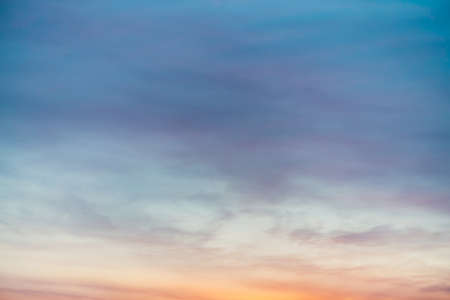 Sunset sky with violet yellow light clouds. Colorful smooth blue sky gradient. Natural background of sunrise. Amazing heaven at morning. Slightly cloudy evening atmosphere. Wonderful weather on dawn.