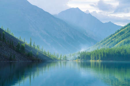 Photo pour Ghostly mountain lake in highlands at early morning. Beautiful misty mountains reflected in calm clear water surface. Smoke of campfires. Amazing atmospheric foggy landscape of majestic nature. - image libre de droit