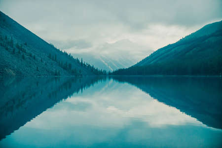 Photo pour Amazing silhouettes of mountains and low clouds reflected on mountain lake. Beautiful ripples on water mirror. Cloudy sky in highlands. Atmospheric ghostly landscape. Wonderful mystic mountainscape. - image libre de droit