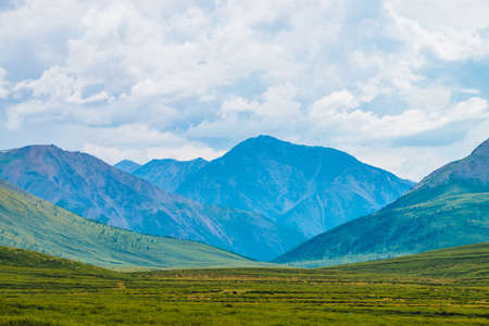 Spectacular view of giant mountains under cloudy sky. Huge mountain range at overcast weather. Wonderful wild scenery. Atmospheric dramatic highland landscape of majestic nature. Scenic mountainscape.