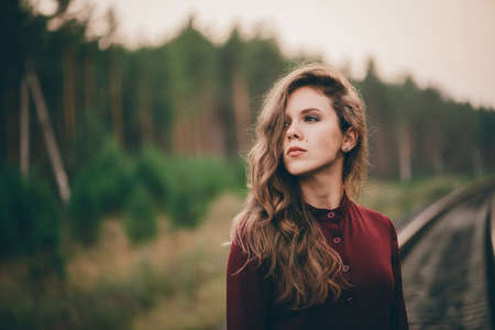 Photo pour Beautiful girl with curly natural hair enjoy nature in forest on railway. Dreamer lady in burgundy dress walk on railroad. Female portrait of inspired girl on rails at dawn. Sun in hair in autumn. - image libre de droit