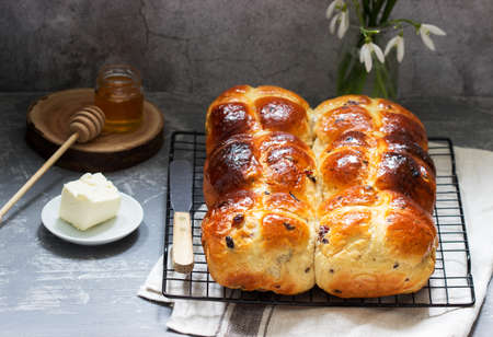 Photo for Traditional hot cross buns with honey and butter on a concrete background. Selective focus. - Royalty Free Image