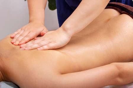 Photo pour Woman doing massage around shoulder blade on nude body - image libre de droit