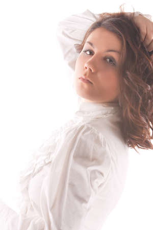 sensual cute caucasian brunette woman standing in white shirt over pure white background.shoot made in high key technique.