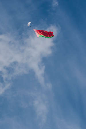 Minsk, Belarus-June 21, 2014: International Parachuterâᅵᅵs Team Performing in Air While Unwinding National Flag of the Republic of Belarus In Front of Spectators During Aviation Sport Event Dedicated to the 80th Anniversary of DOSAAF Foundation in Mi