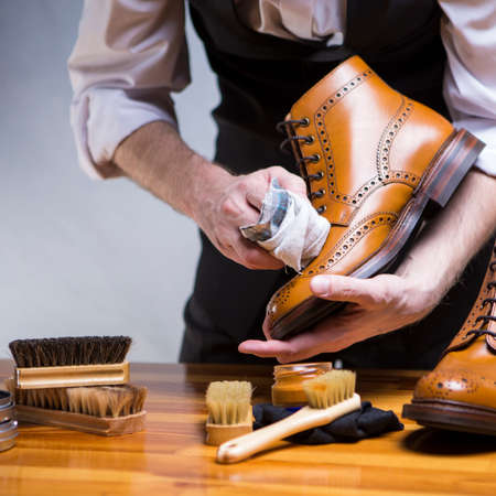 Photo pour Footwear Ideas and Concepts. Extreme Close Up of Mans Hands Cleaning Luxury Calf Leather Brogues with Special Cloth and Shoe Wax. Square Orientation - image libre de droit