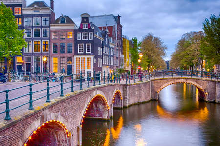 Foto de Nighview of Amterdam Cityscape with Its Canals. Illuminated Bridge and Traditional Dutch Houses At Twilight on The Background. Horizontal Shot - Imagen libre de derechos