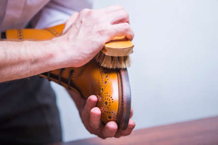 Photo pour Footwear Concepts. Closeup of Male Hands with Polishing Brush for Tan Brogue Derby Boots.  Horizontal Image Composition - image libre de droit