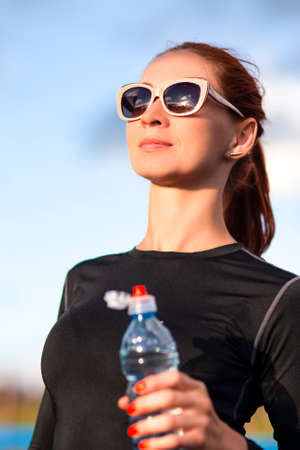 Photo for Fitness Caucasian Woman in Sportwear and Sunglasses With Water from Bottle Outdoors.Vertical image - Royalty Free Image