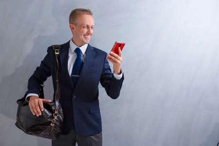 Photo pour Portrait of Positive Caucasian Male Businessman with Leather Messenger bag and Smartphone. Posing Against Grey Wall.Horizontal image - image libre de droit
