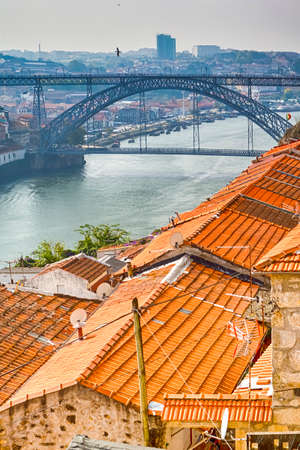 Photo pour Travel Places Concepts. Traditional Rooftops of Porto Houses at Daytime with Ponte Infante D Henrique in Background in Portugal. Vertical Image - image libre de droit